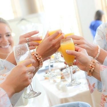 Bride and bridesmaids share a mimosa toast before the wedding reception at Hazeltine National Golf Club