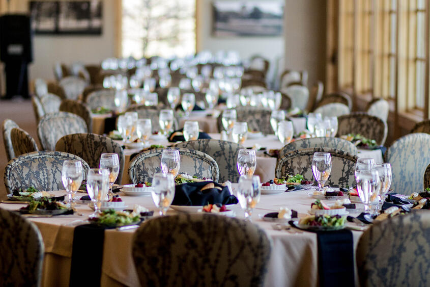 Banquet tables set for a lunch meeting overlooking the golf course at Hazeltine National Golf Club