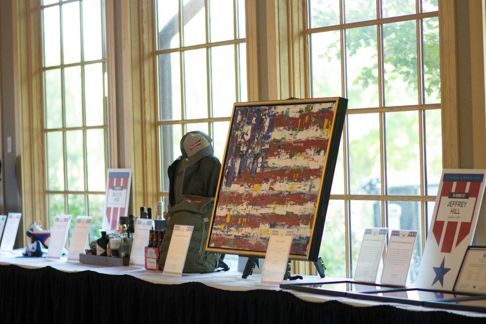 Silent auction of a fundraising gala set against the backdrop of  the golf course at Hazeltine National Golf Club