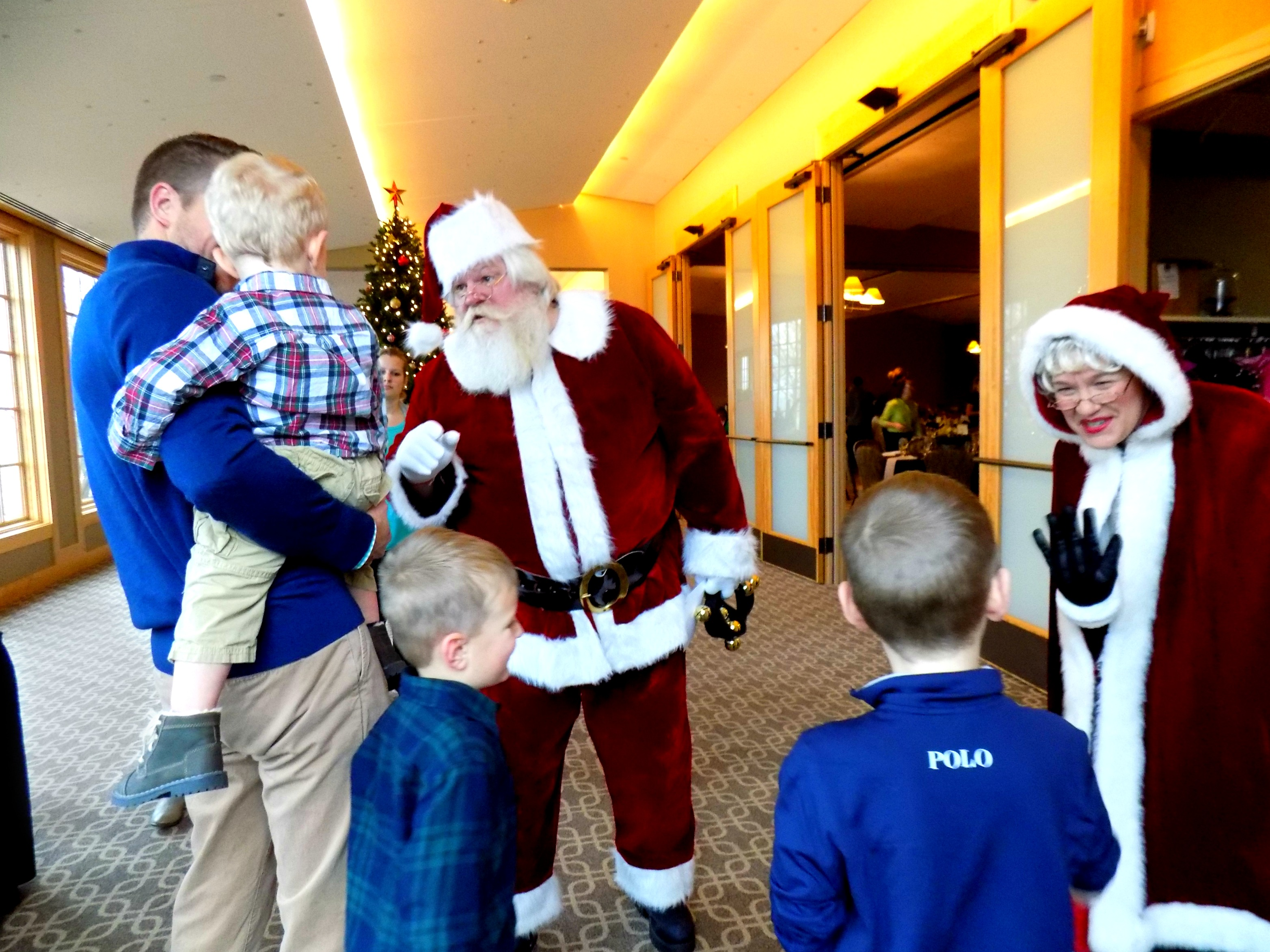 Santa and Mrs. Clause greeting children at a holiday party at Hazeltine National Golf Club