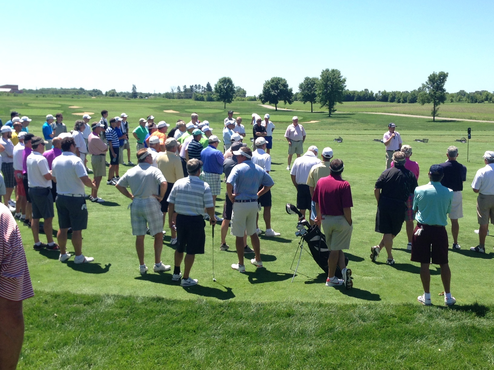 Golfers listen to rules before a private golf tournament at Hazelitne National Golf Club
