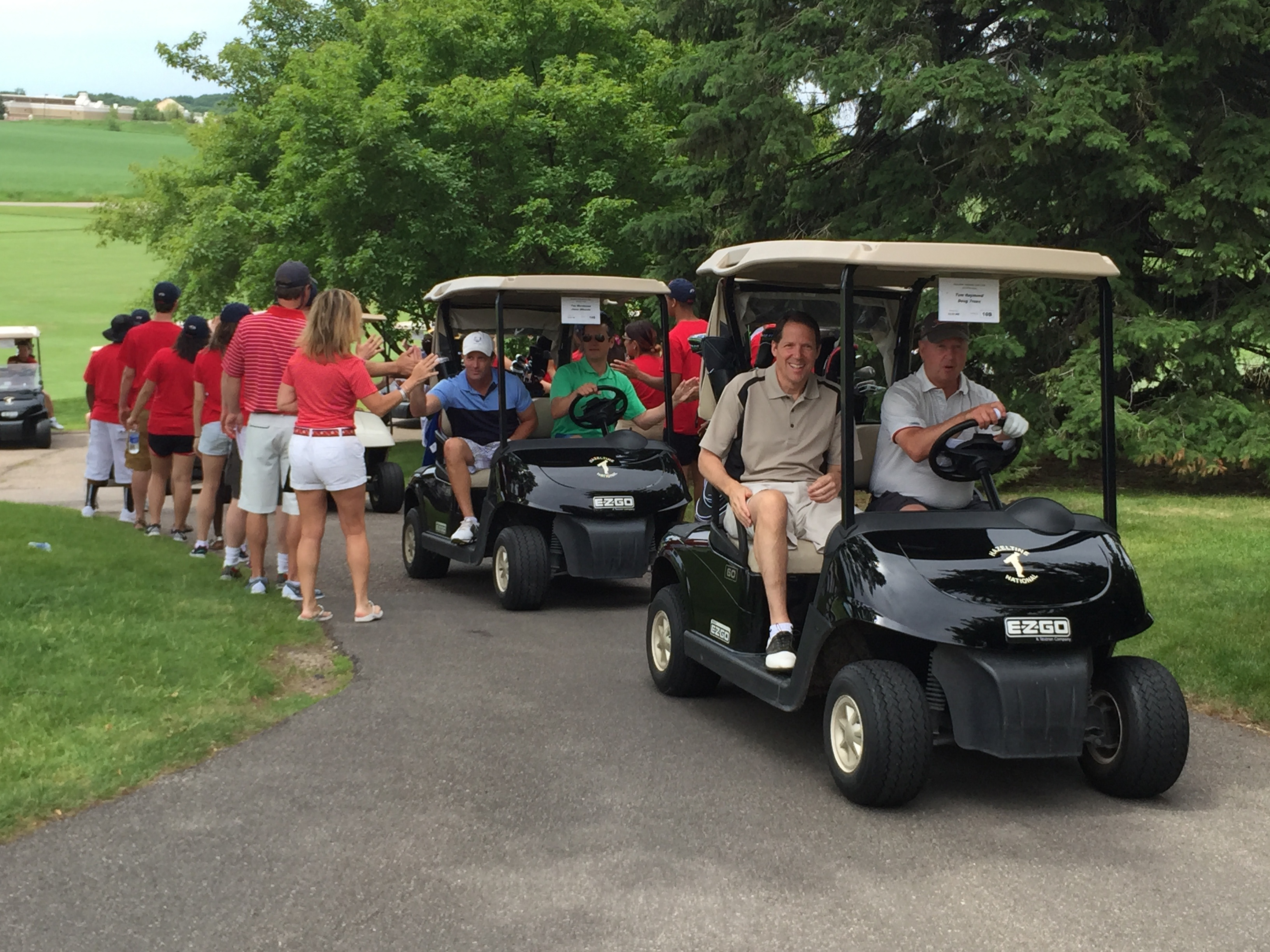 Players head out to the shotgun start of a private golf tournament at Hazeltine National Golf Club