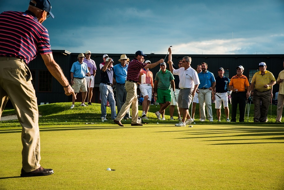 Golfers participate in a putting contest during a private golf tournament at Hazeltine National Golf Club