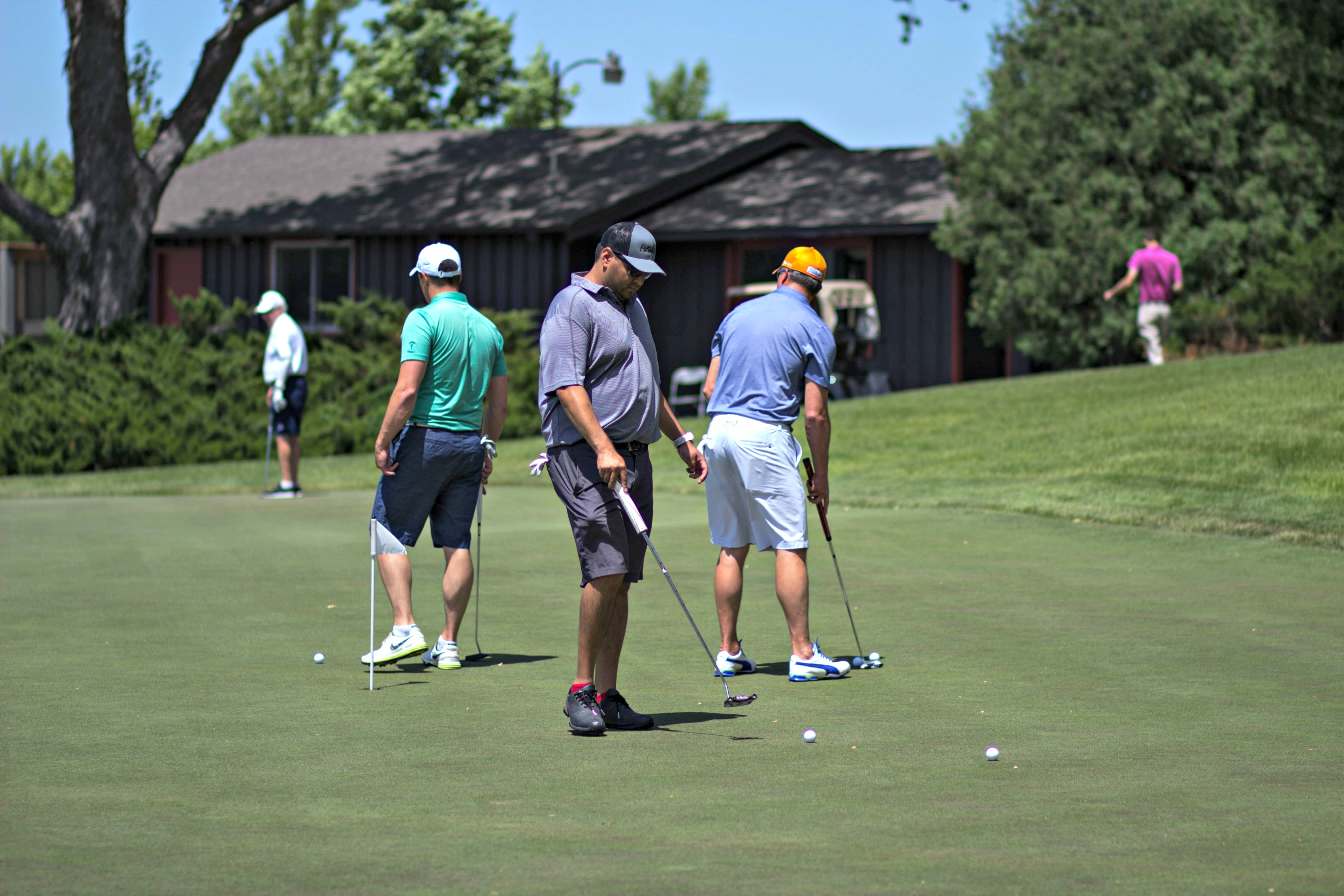 Golfers practice putting during a golf networking event at Hazeltine National Golf Club
