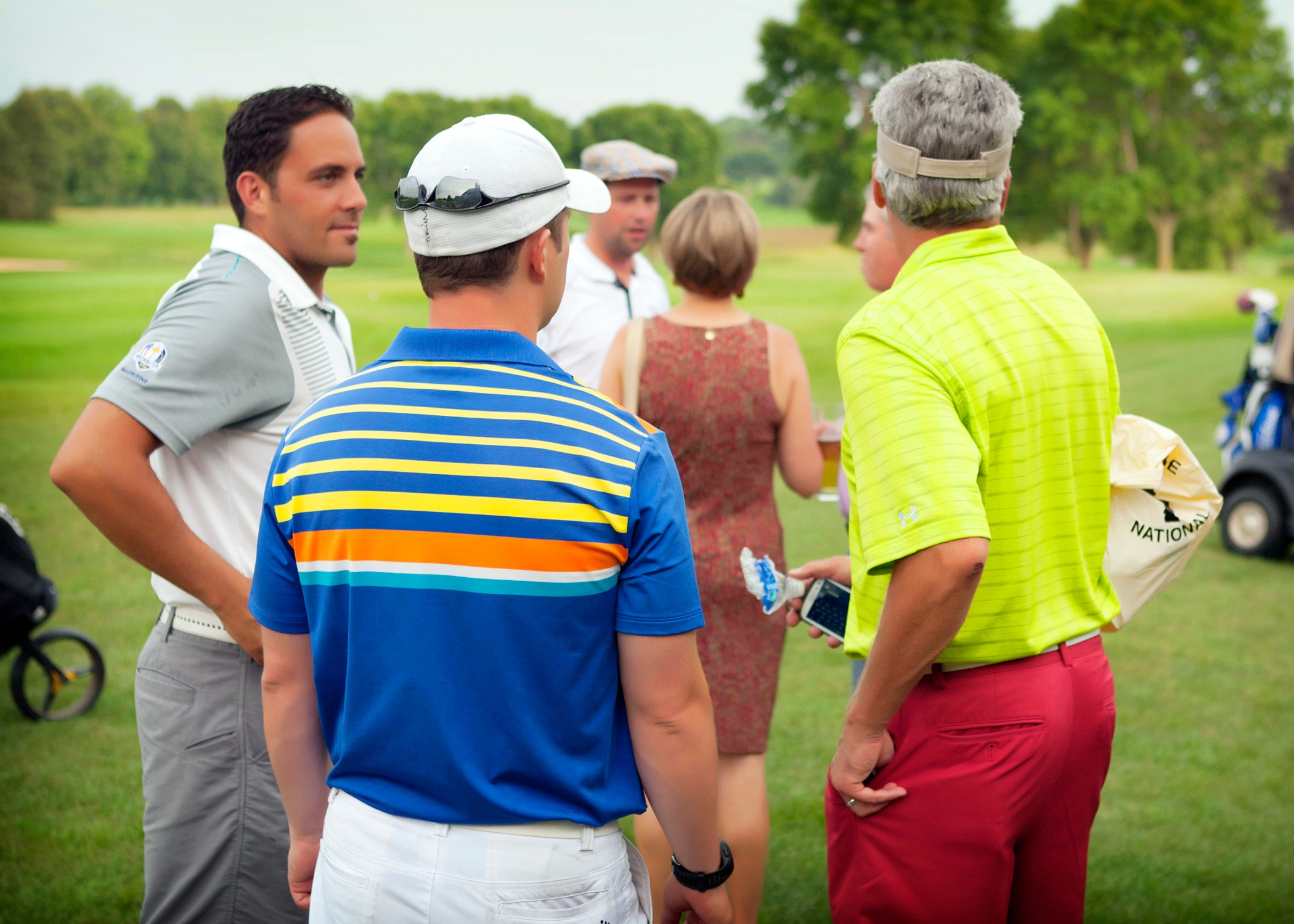 Golfers chatting after finishing play in a private golf tournament at Hazeltine National Golf Club
