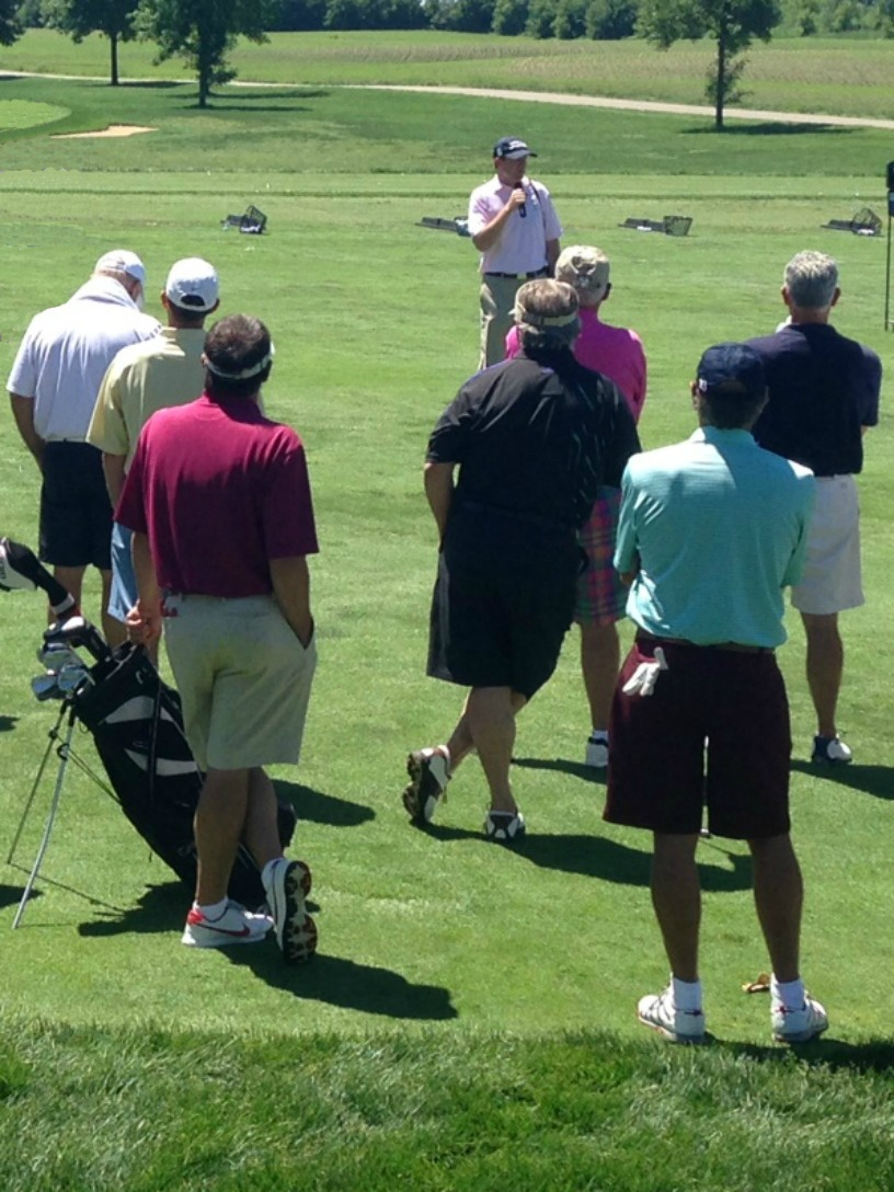 Golfers listen to instruction during a business networking event at Hazeltine National Golf Club