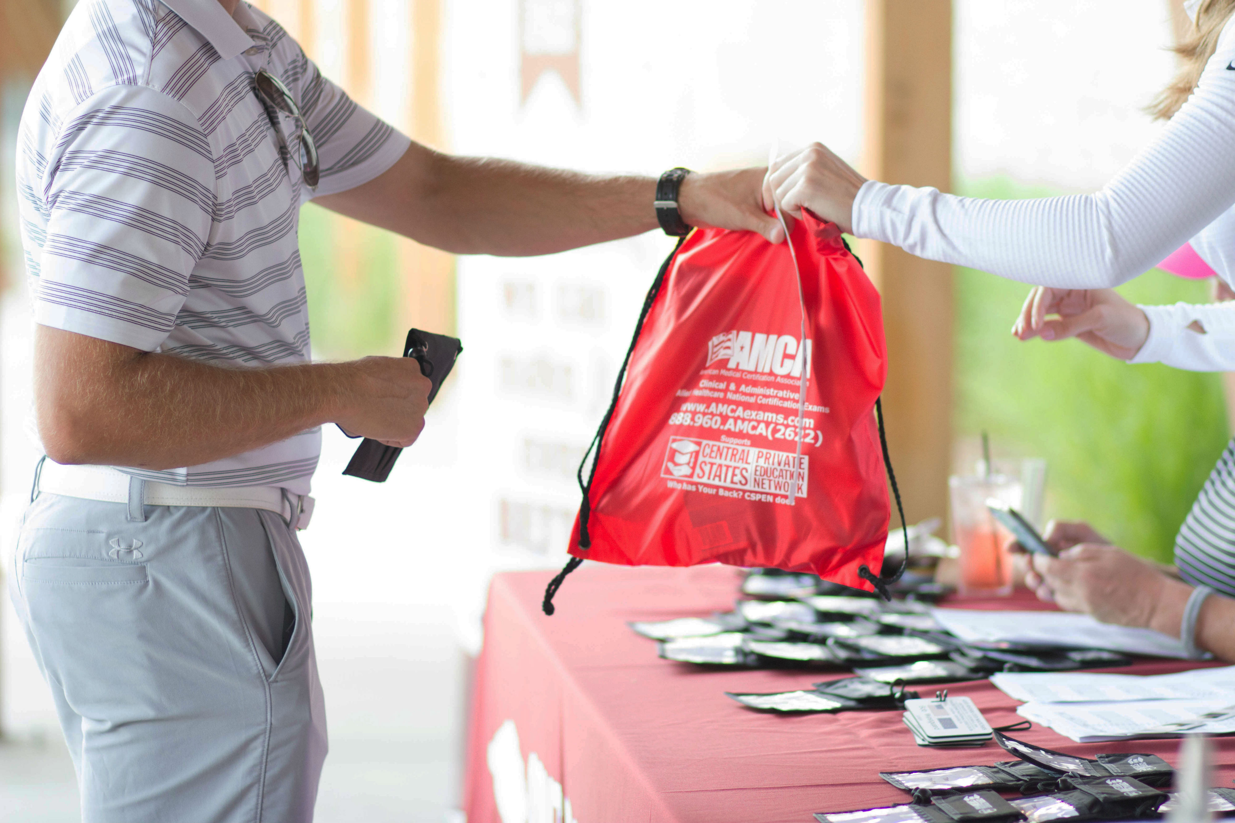 Golfers are greeted at registration at a private golf tournament at Hazeltine National Golf Club