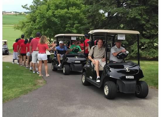 Golfers head to the first hole for a shotgun start of a  golf tournament at Hazeltine National Golf Club