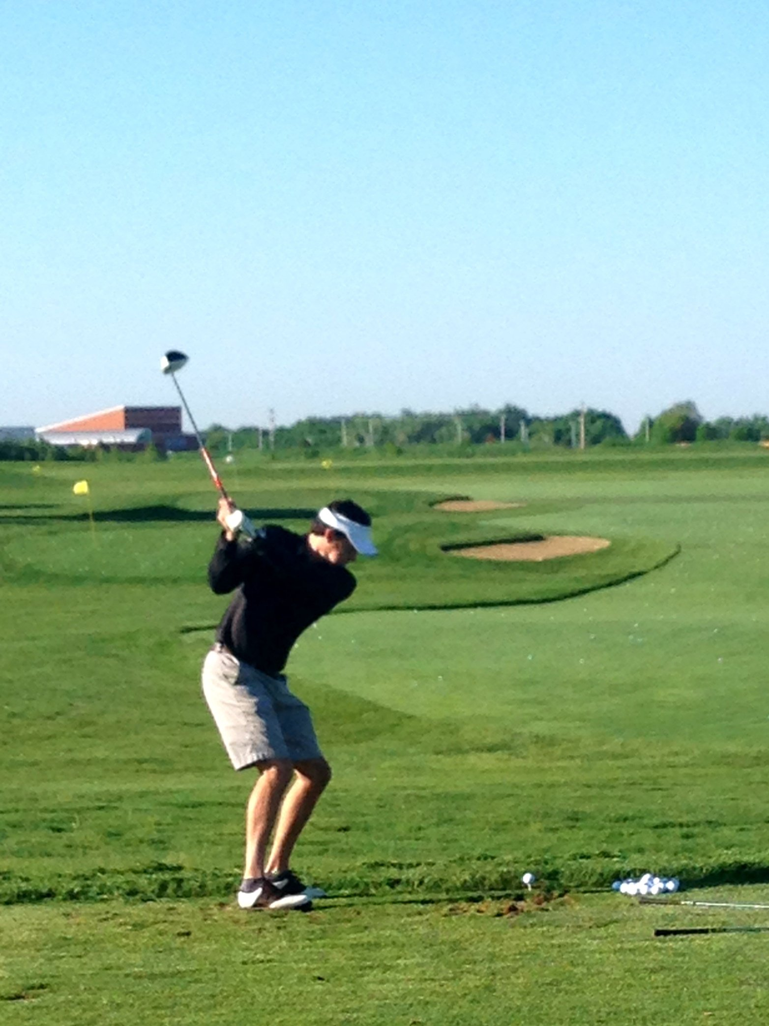 Golfer hitting balls on the practice range at Hazeltine National Golf Club before a private golf touranment