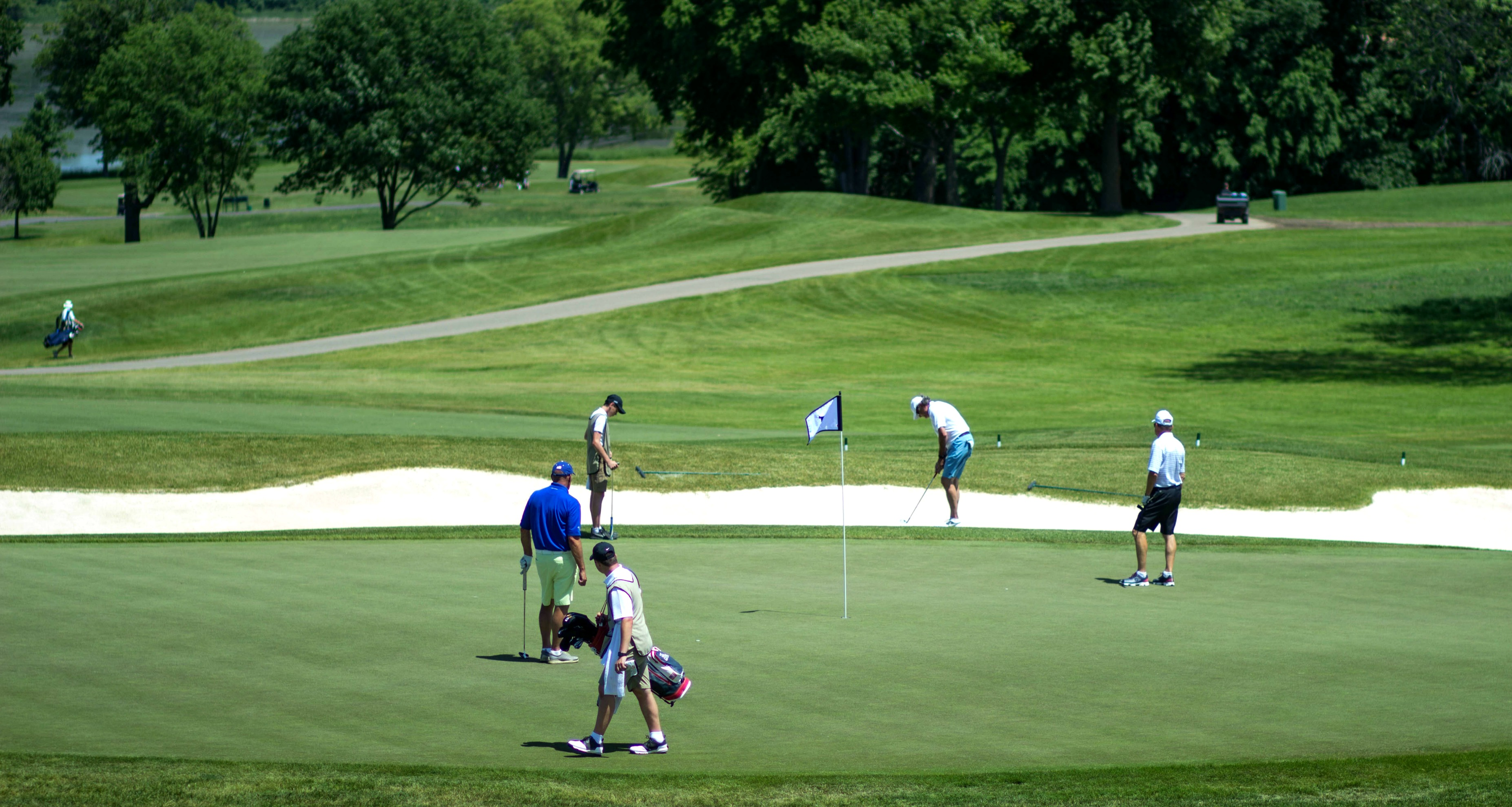 Golfers and caddies on the green during a private golf tournament at Hazeltine National Golf Club