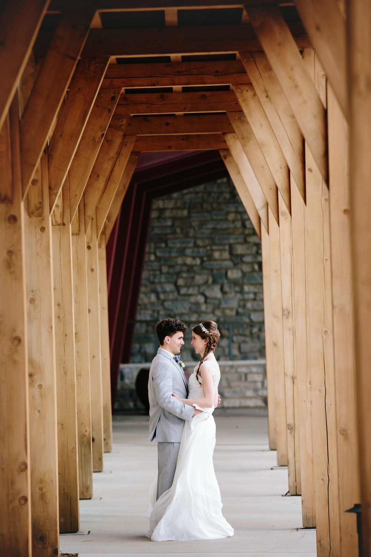 Couple under arch at before their wedding reception at Hazeltine National Golf Club